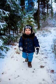 Mały wesoły chłopiec 2 lata w niebieskiej kurtce spaceruje po zimowym lesie