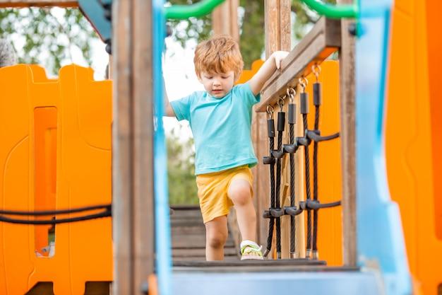 Mały wesoły chłopiec na placu zabaw