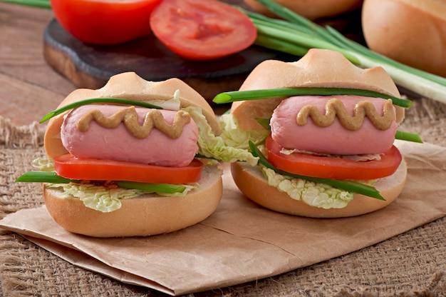Mały wesoły hot dog z kiełbasą i pomidorem