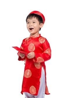Mały wietnamski chłopiec trzymający czerwone koperty dla tet. słowo oznacza podwójne szczęście. jest to prezent w księżycowy nowy rok lub święto tet na czerwonym tle izolowania.