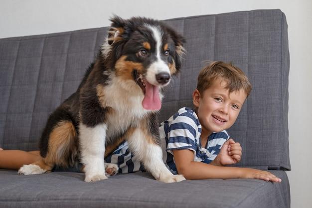 Mały właściciel szczęśliwy chłopiec kładzie się z psem owczarkiem australijskim na kanapie. trzy kolory.