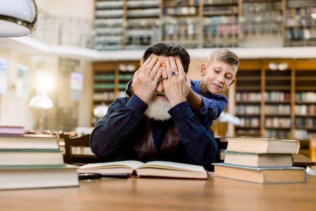 Mały wnuk zamyka dłońmi oczy dziadka, siedzącego przy stole i czytającego książki w zabytkowej bibliotece. zgadnij, kto tam jest.