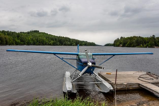 Mały wodnosamolot przycumowany do pływającego drewnianego pontonu w pobliżu brzegu górskiego jeziora