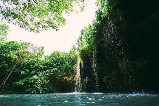 Mały wodospad i jezioro otoczone latem drzewami. cudowny krajobraz u ujścia rzeki.