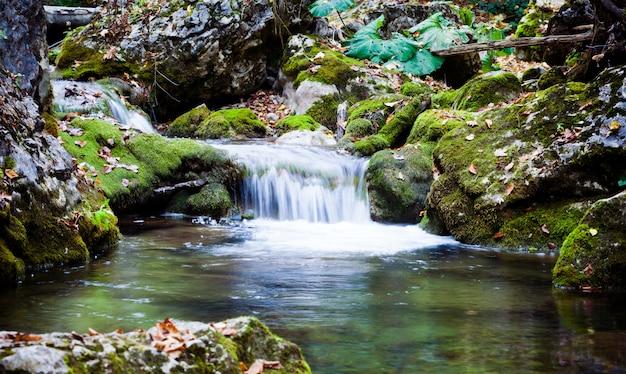 Mały wodospad i laguny z czystą, spokojną wodą otoczone zielonymi wzgórzami w letni dzień