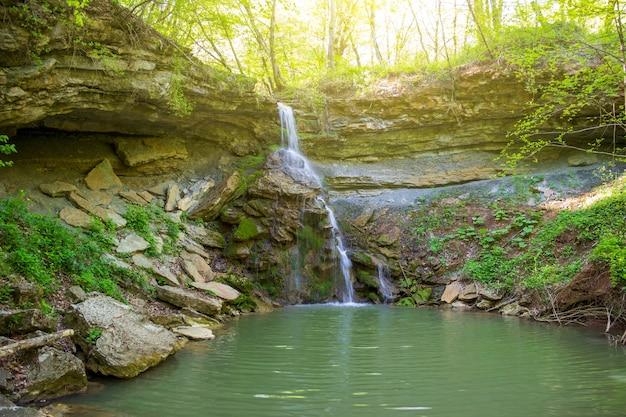 Mały wodospad na leśnym strumieniu w słoneczny wiosenny lub letni poranek
