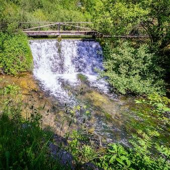 Mały wodospad pod drewnianym mostem u źródła rzeki ebro. fontibre kantabria.