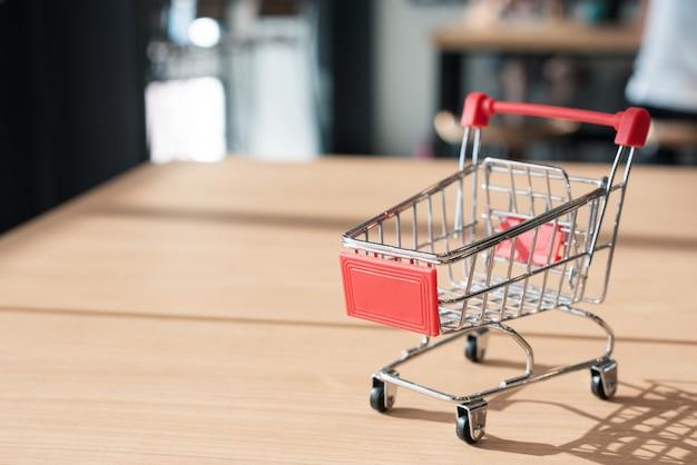 Mały wózek na zakupy na drewnianym stole