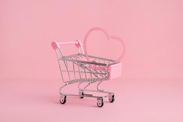 Mały wózek na zakupy na różowym tle, kopia przestrzeń, zakupy i koncepcja miłości widok z boku