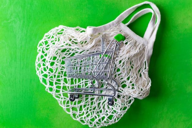Mały wózek na zakupy nad siatkową torbą na zielono