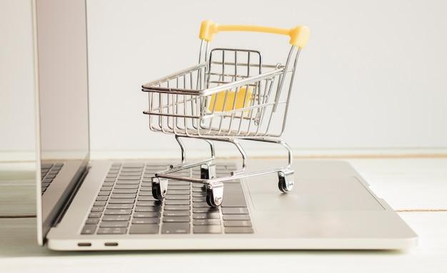 Mały wózek na zakupy stojący na laptopie