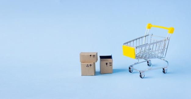 Mały wózek spożywczy i pudełka z towarami na niebieskim tle, wolne miejsce na tekst