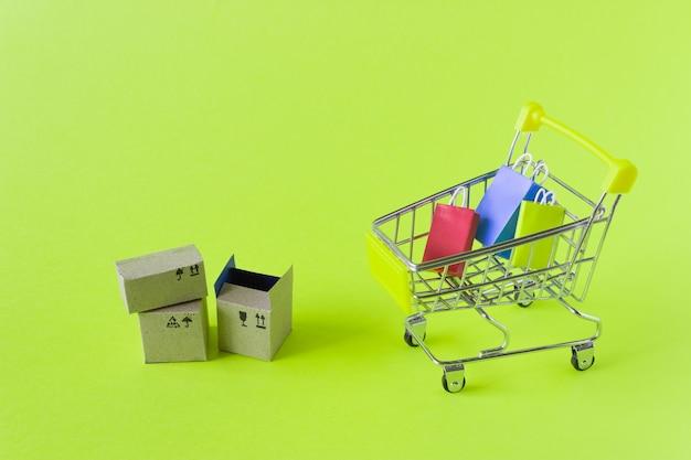 Mały wózek spożywczy z pudełkami i torbami na zielonym tle