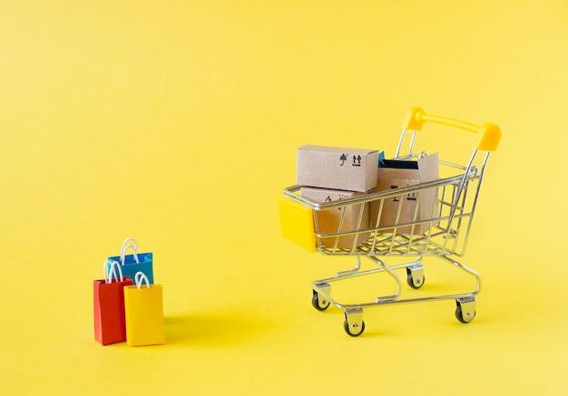 Mały wózek spożywczy z pudełkami i torbami na żółtym tle