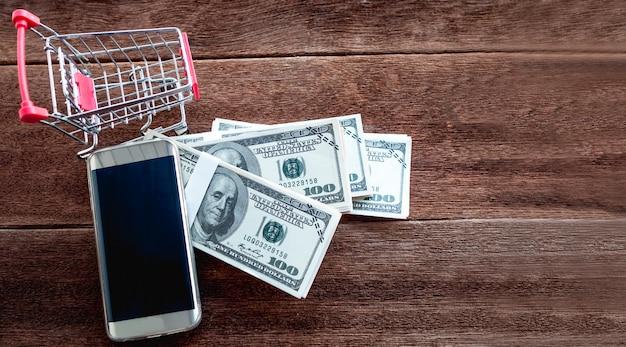 Mały wózek z pieniędzmi dolara i telefon komórkowy postawiony na drewnianej podłodze mają miejsce. koncepcja zakupów online.