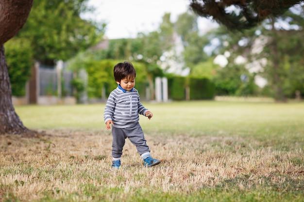 Mały wschodni przystojny chłopczyk bawi się na świeżym powietrzu w parku