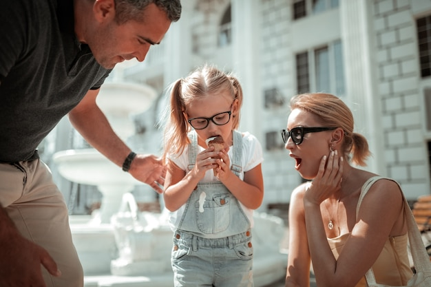 Mały wypadek. mała dziewczynka brudzi się jedząc topniejące lody w pobliżu wspierających rodziców na ulicy.