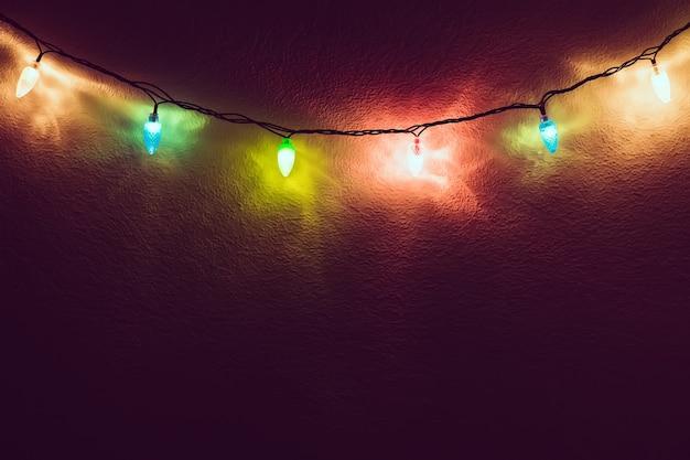 Mały wystrój świecy na drewnianej ramie na wigilię bożego narodzenia lub nowego roku. ciepłe ładne wnętrze świecące światłem w ciemnym pomieszczeniu. skopiuj miejsce na tekst.