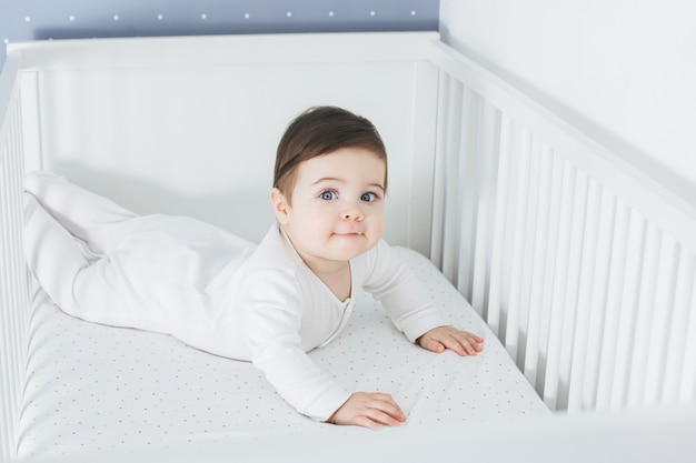 Mały zabawny chłopiec, leżąc w łóżeczku i śmiejąc się