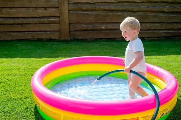 Mały zabawny chłopiec zbierający wodę w basenie dla dzieci