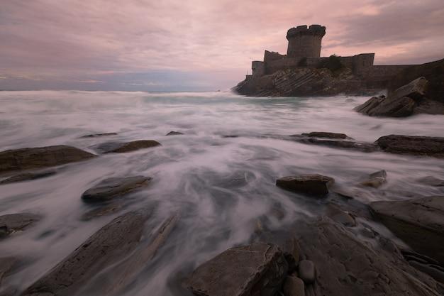 Mały zamek otoczony odważnym oceanem atlantyckim w sokoa (socoa) w zatoce donibane lohitzune (saint jean de luz) w kraju basków.