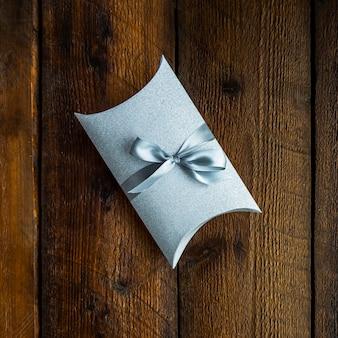Mały zawinięty prezent na drewniane tła