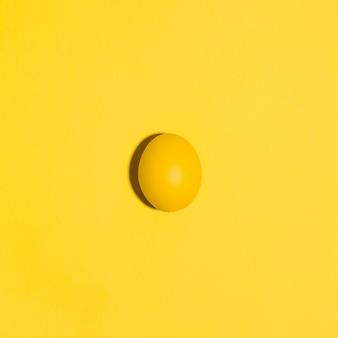 Mały żółty wielkanocny jajko na koloru żółtego stole