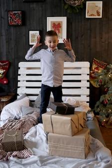 Mały zszokowany chłopiec z prezentami świątecznymi