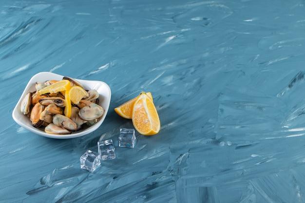 Małże bez muszli i pokrojone w plasterki cytryny w misce, na marmurowym tle.