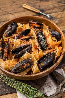 Małże i małże mafaldine mafaldine z sosem pomidorowym w rustykalnym drewnianym talerzu. drewniane tło. widok z góry.