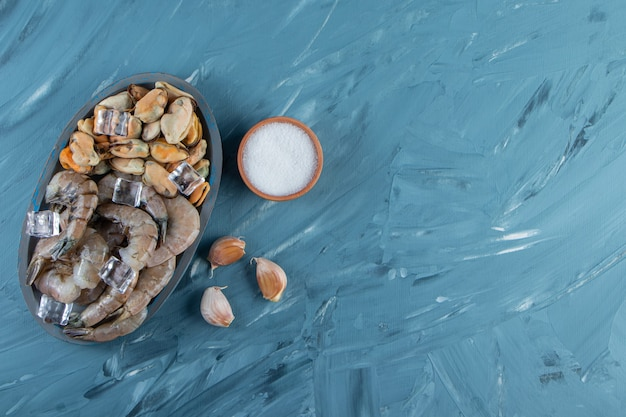 Małże, krewetki i kostki lodu na drewnianym talerzu, na marmurowym tle.