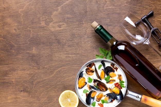 Małże o płaskim łożu w białym sosie i wino z copyspace