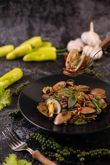 Małże smażone curry w proszku na czarnym talerzu.