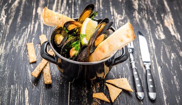 Małże w metalowym naczyniu do gotowania i francuska bagietka z ziołami