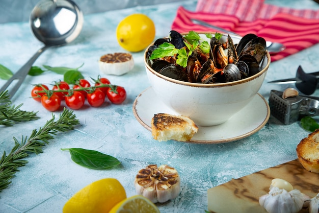 Małże w talerzu podawane z pomidorami, tostami, cytryną i czosnkiem