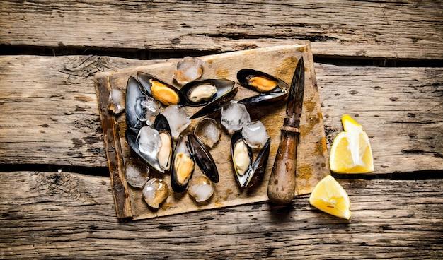Małże z cytryną i lodem na drewnianej desce. na drewnianym tle. widok z góry
