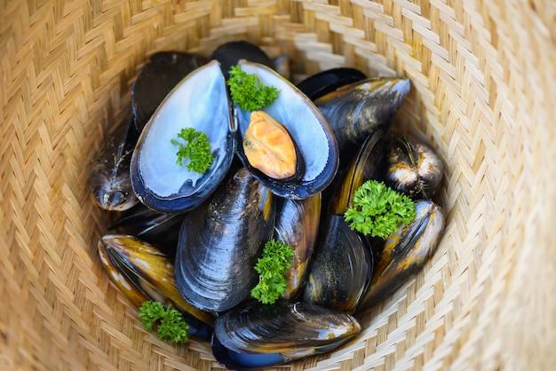 Małże z ziołami cytrynowymi na parze gotować jedzenie. świeże owoce morza skorupiaki w restauracji muszli muszli żywności na bambusowym koszyku parowca