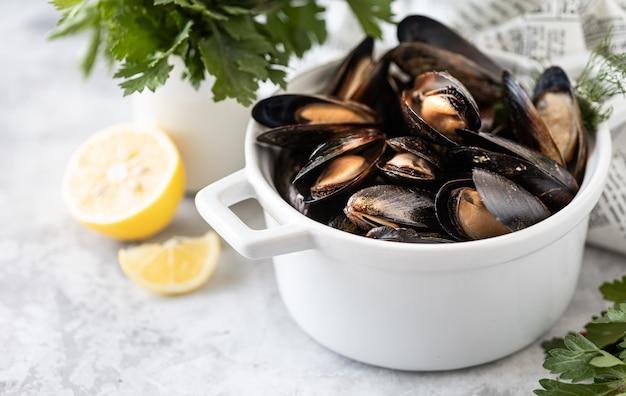 Małże ze świeżymi ziołami i cytryną na białej patelni na betonie. owoce morza dla smakoszy.