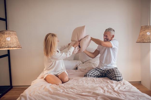 Małżeństwo bawi się w sypialni i walczy z poduszkami