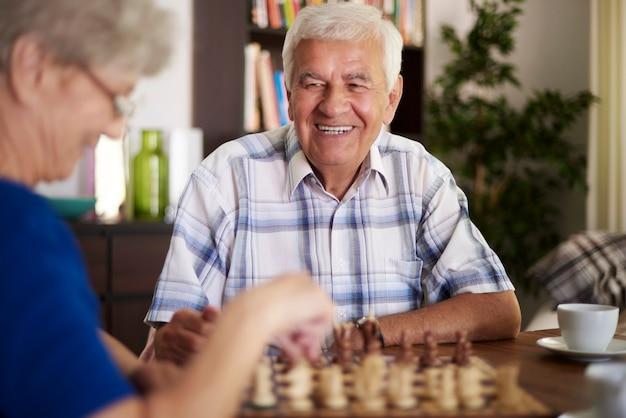 Małżeństwo gra w szachy w salonie