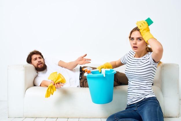 Małżeństwo przy kanapie sprzątanie mieszkania świadczenie usług. zdjęcie wysokiej jakości