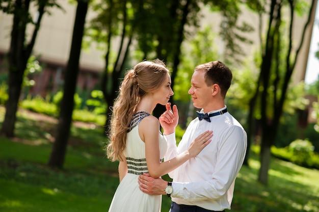 Małżeństwo spaceruje i obejmuje się w parku.