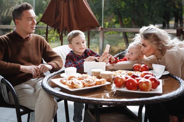 Małżeństwo z dziećmi, córką i synem przy stole w kawiarni. szczęśliwa para tradycyjnych, szczęście rodzinne.
