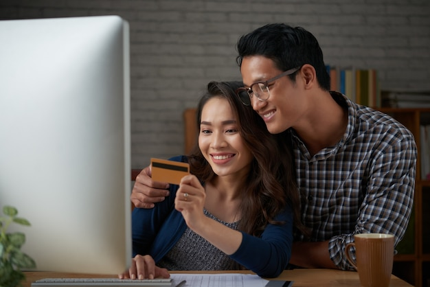 Małżonkowie dokonujący płatności za pomocą karty kredytowej w sklepie internetowym