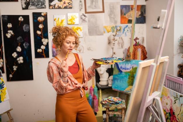 Mam nowy pomysł. kręcona artystka z brązowymi włosami trzyma w ustach pędzel do malowania, mając nowy pomysł