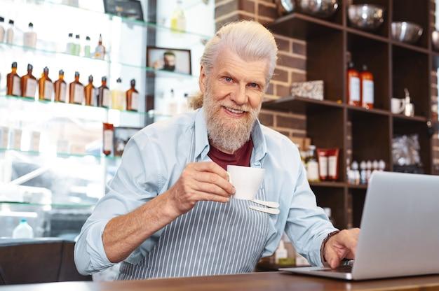 Mam pauzę. radosny brodaty mężczyzna trzyma kubek w prawej ręce, patrząc prosto w kamerę