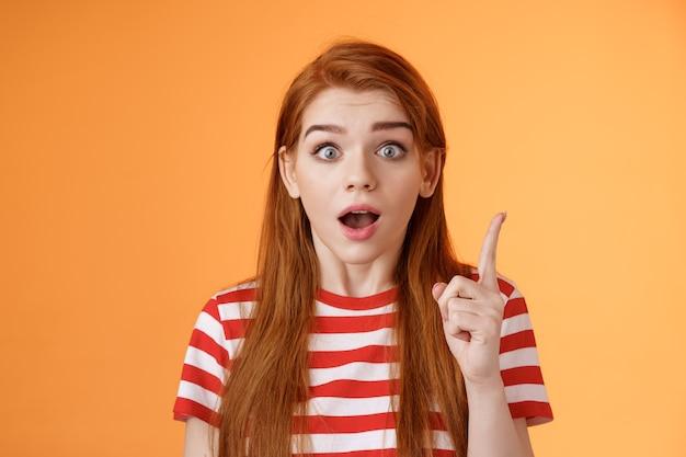 Mam pomysł. podekscytowana rudowłosa kobieta dzieląca się ciekawym planem, podnieś palec wskazujący gest eureka, otwarte usta powiedz myśl, pamiętaj o ważnej rzeczy, wpatruj się w aparat oszołomiony, w końcu zrozum