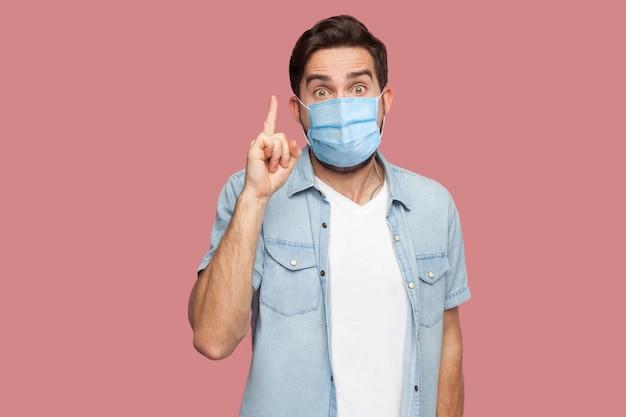 Mam pomysł. portret zaskoczony młody człowiek z chirurgiczną maską medyczną w niebieskiej koszuli stojący ze zdumioną twarzą, patrzący na kamerę ze znakiem pomysłu. strzał w studio, na białym tle na różowym tle