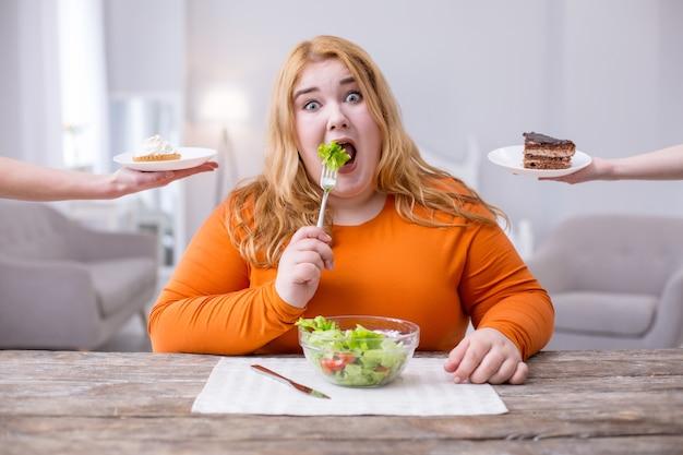 Mam problem. kobieta z nadwagą o słabej woli jedząca zdrowe śniadanie i myśląca o ciasteczkach