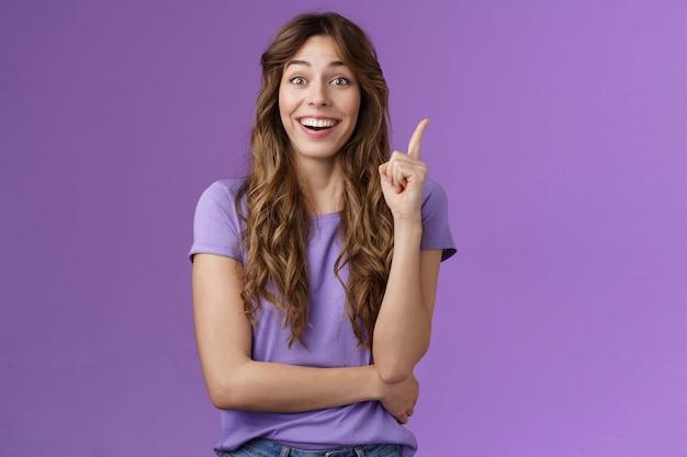 Mam świetny pomysł. atrakcyjna wesoła kędzierzawa kobieta podnosi palec wskazujący eureka gest uśmiechając się szeroko podjęta decyzja wymyślić dobry plan akcji myśli uśmiechając się w zasadzkę fioletowym tle.